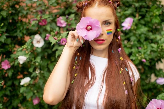 Menina alegre com arco-íris lgbt no rosto, posando em flores desabrochando