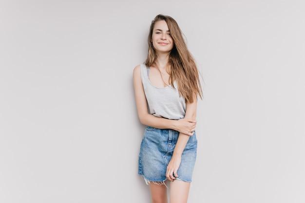Menina alegre com cabelo castanho claro posando. foto interna de uma espetacular senhora caucasiana em saia jeans sorrindo