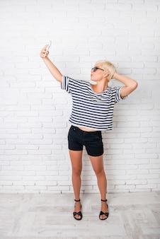 Menina alegre com cabelo curto que faz foto selfe