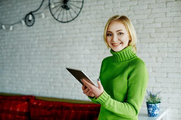 Menina alegre com cabelos claros, suéter verde, sentado no café com tablet, conceito freelance, compras online, retrato.