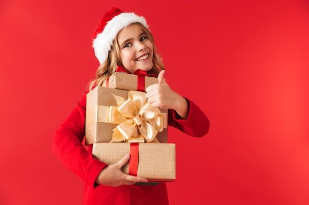Menina alegre com fantasia de natal, isolada, segurando caixas de presente