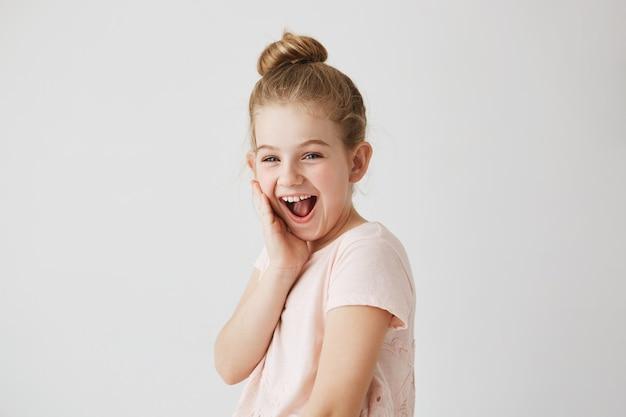 Menina alegre com olhos azuis e penteado coque com expressão feliz depois de se ver no espelho com um belo penteado novo.