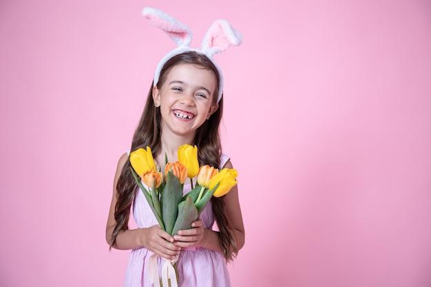 Menina alegre com orelhas de coelhinho da páscoa sorri e tem um buquê de tulipas nas mãos em um fundo rosa do estúdio.