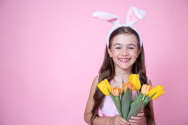 Menina alegre com orelhas de coelho da páscoa sorri e segura um buquê de tulipas em um estúdio rosa