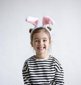 Menina alegre com orelhas decorativas de coelhinho da páscoa na cabeça.