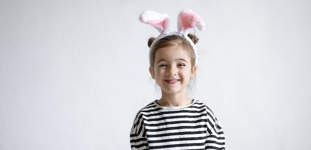 Menina alegre com orelhas decorativas de coelho da páscoa na cabeça