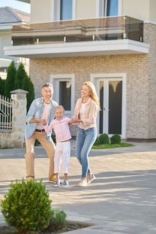 Menina alegre com papai e mamãe na rua