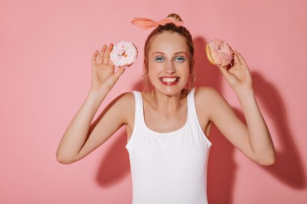 Menina alegre com penteado loiro em brincos e maquiagem legal em roupas brancas sorrindo e segurando dois donuts na parede isolada
