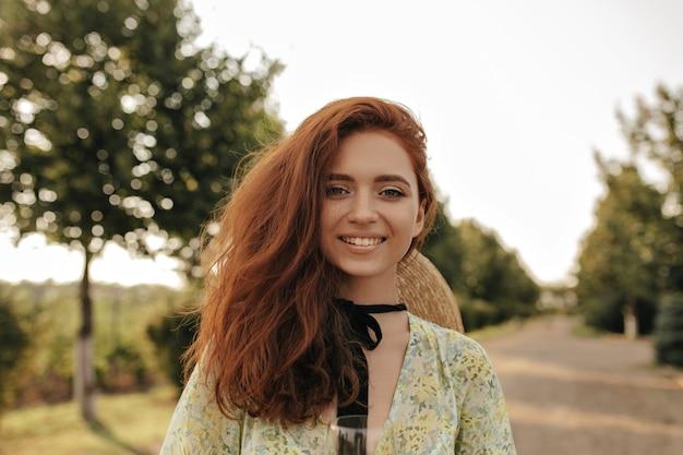 Menina alegre com penteado ruivo ondulado e bandagem preta no pescoço, com vestido elegante de verão e chapéu de palha, sorrindo e olhando para a frente ao ar livre