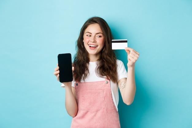Menina alegre com roupas de verão, mostrando a tela do smartphone e um cartão de crédito de plástico, pagando online, fazendo compras, em pé sobre um fundo azul