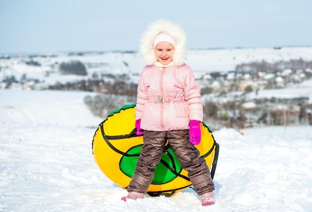 Menina alegre com tubo de neve