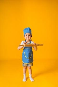 Menina alegre com um chapéu e avental de chef segurando um rolo em uma superfície amarela com espaço para texto