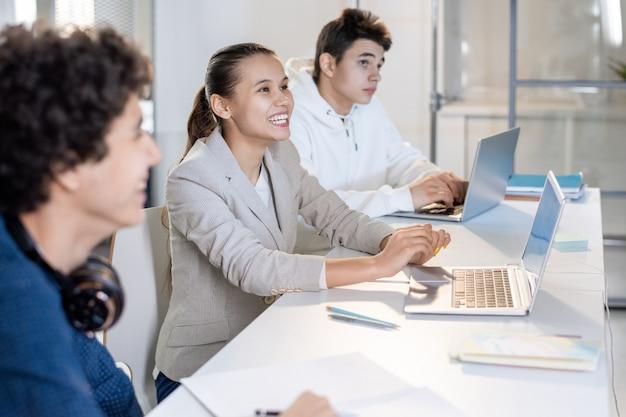 Menina alegre com um sorriso dentuço sentada entre seus colegas de classe na conferência e olhando para a tela enquanto faz uma apresentação