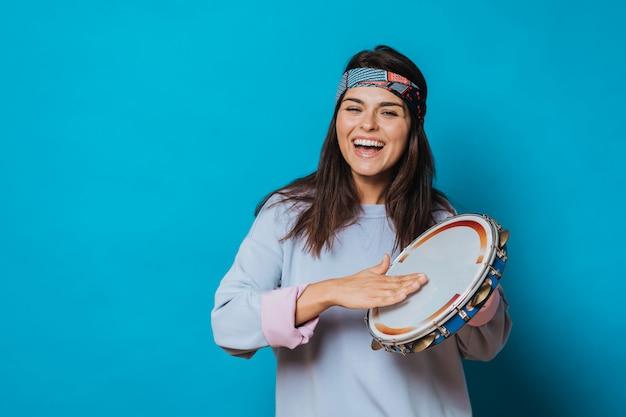 Menina alegre com uma faixa na cabeça e suéter cinza tocando pandeiro e rindo alegremente sobre fundo azul.