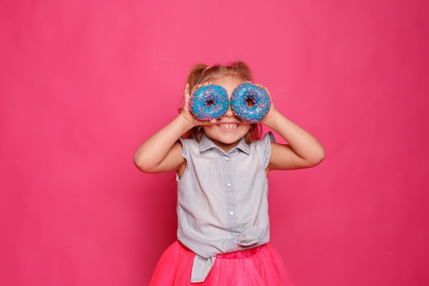 Menina alegre com uma rosquinha em um fundo rosa. a criança se entrega à comida. diversão com rosquinhas
