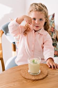 Menina alegre de cabelo encaracolado, de camisa rosa, comendo um smothie verde em um café
