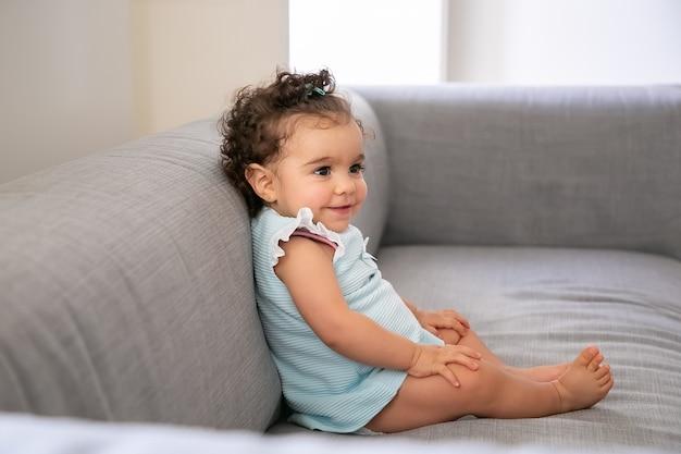 Menina alegre de cabelos cacheados escuros, vestindo um pano azul claro, sentada no sofá cinza em casa, olhando para longe e sorrindo. criança em casa e conceito de infância