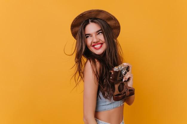 Menina alegre de chapéu rindo e curtindo a sessão de fotos no espaço amarelo