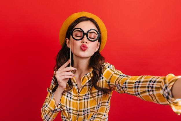 Menina alegre de chapéu segura óculos na vara e manda beijo. adolescente em camisa amarela leva selfie na parede vermelha.