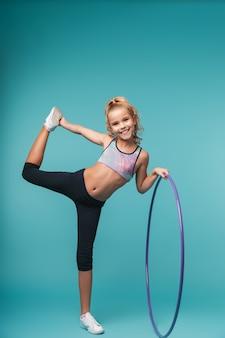 Menina alegre de esportes fazendo exercícios com um bambolê isolado na parede azul
