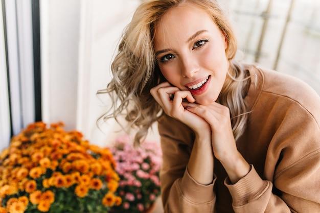 Menina alegre de olhos escuros sorrindo. mulher loira romântica posando com flores laranja.