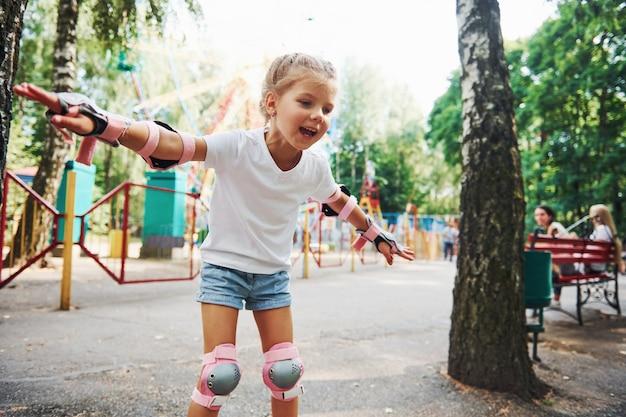 Menina alegre de patins se divertindo no parque perto das atrações