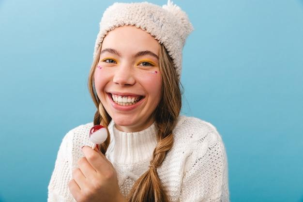 Menina alegre de suéter isolada, comendo pirulito