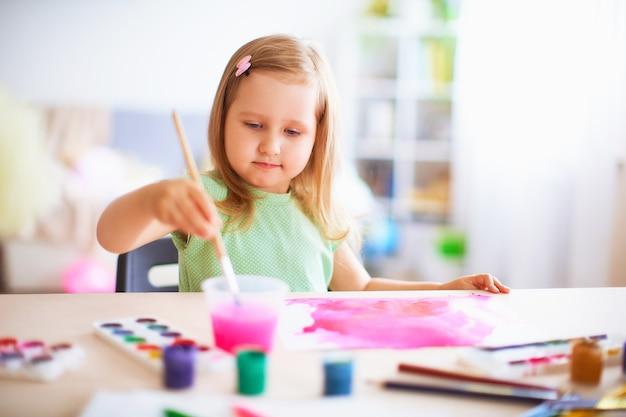 Menina alegre desenha guache em cores diferentes em uma folha de papel branca.
