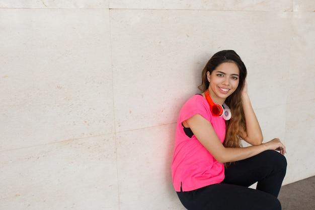 Menina alegre desportiva, treinamento ao ar livre e descansando