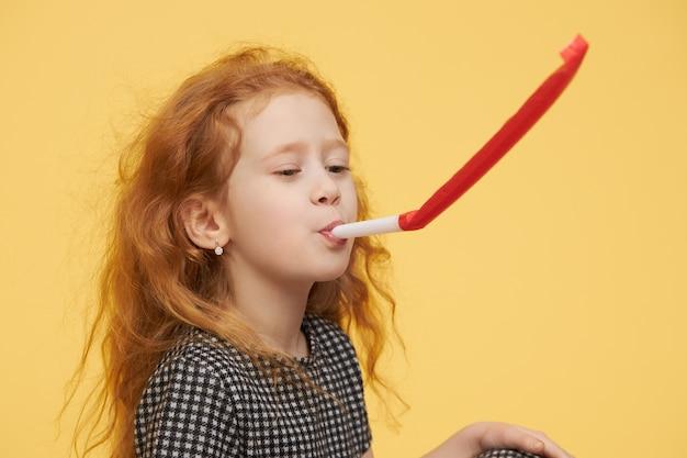 Menina alegre e brincalhona com longos cabelos ruivos soprando uma buzina de festa