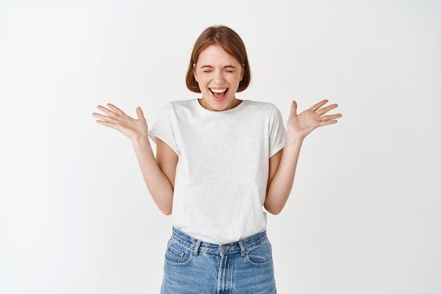 Menina alegre e cândida, rindo e pulando de alegria e felicidade, vencendo e comemorando, levantando as mãos surpresa, encostada na parede branca