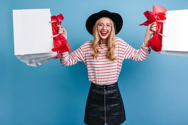 Menina alegre e elegante segurando sacolas de compras e rindo. vista frontal da jovem loira com chapéu.