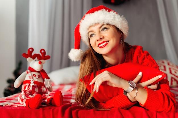 Menina alegre e encantadora deitada na cama, abraçando o travesseiro vermelho e usando chapéu de papai noel