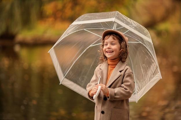 Menina alegre e feliz com um guarda-chuva transparente em uma caminhada no outono à beira do lago