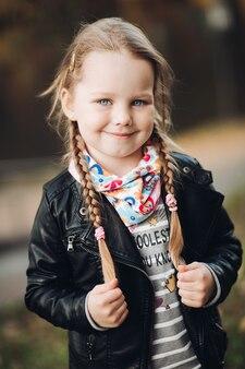 Menina alegre e feliz em roupas quentes, sorrindo e curtindo a vida