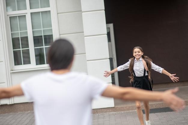 Menina alegre e feliz em uniforme escolar de braços abertos, correndo da escola para a mãe