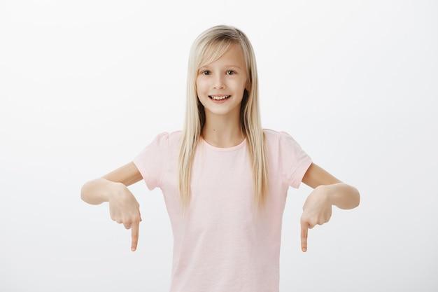 Menina alegre e fofa apontando os dedos para baixo