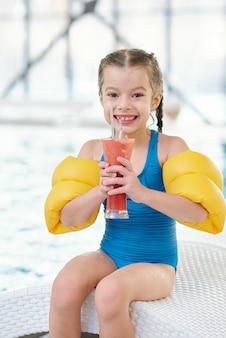 Menina alegre e fofa em trajes de banho segurando um copo de suco ou coquetel enquanto está sentada na espreguiçadeira em frente à câmera ao lado da piscina, depois de nadar