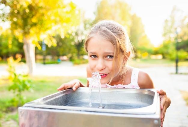 Menina alegre e maravilhosa bebe água fresca de uma pequena fonte em um parque ensolarado e quente de verão
