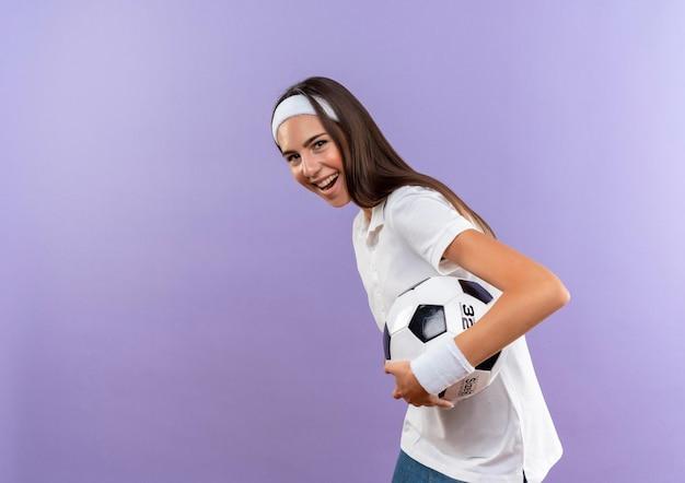 Menina alegre e muito esportiva usando bandana e pulseira, segurando uma bola de futebol em pé na vista de perfil, isolada na parede roxa com espaço de cópia