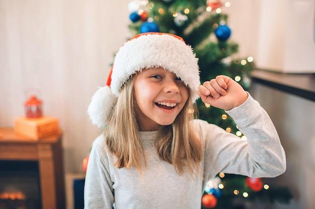 Menina alegre e positiva mantém a borda de seu chapéu de natal.