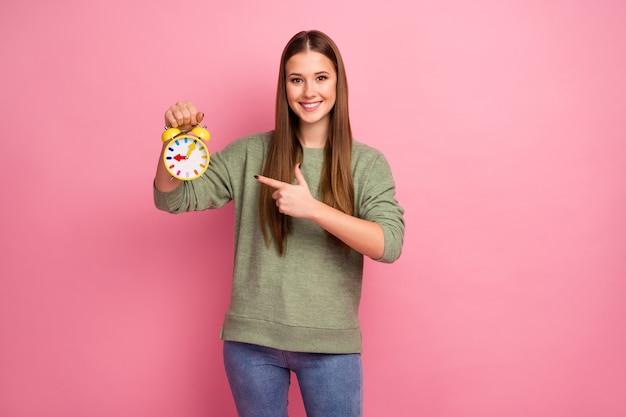 Menina alegre e positiva segurando o relógio, apontando o dedo indicador