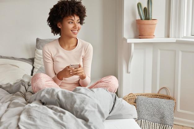 Menina alegre e relaxada de pele escura sentada em uma cama confortável