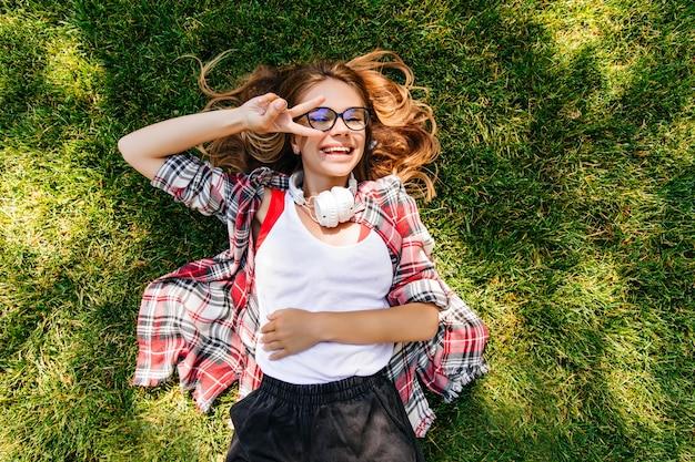Menina alegre em fones de ouvido brancos deitada na grama com um sorriso. tiro aéreo ao ar livre de mulher elegante relaxando no gramado.