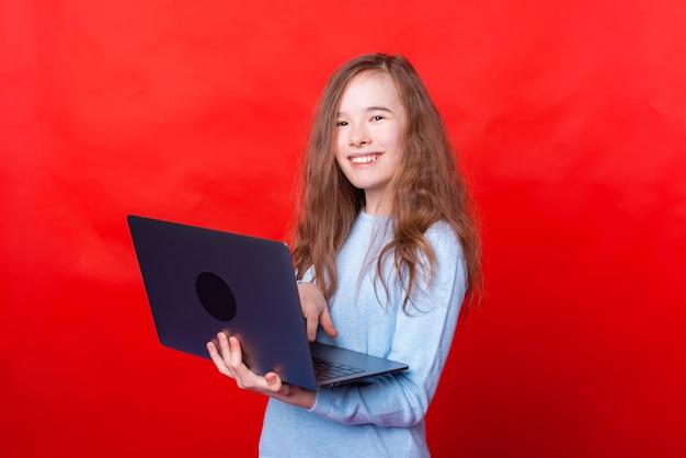 Menina alegre em pé sobre a parede vermelha e usando o laptop