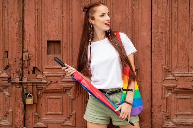 Menina alegre em roupas coloridas, posando sobre a porta velha.