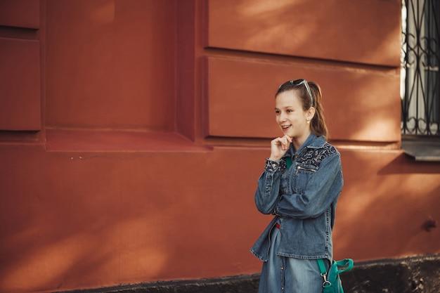 Menina alegre em roupas jeans fica perto de um antigo prédio bonito restaurado.