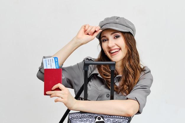 Menina alegre em um chapéu com passagens aéreas e bagagem