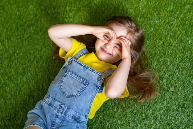 Menina alegre em um macacão jeans, encontra-se em um prado verde