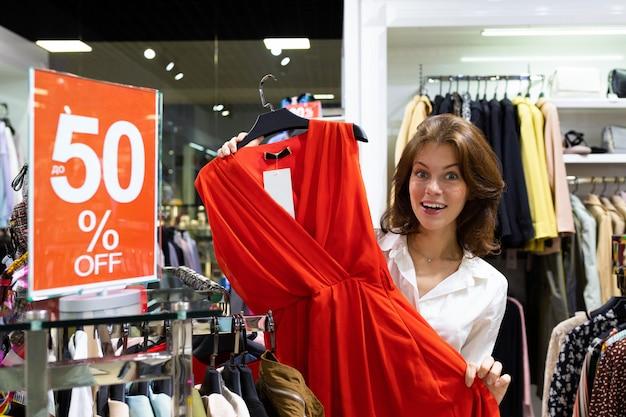 Menina alegre em uma camisa branca escolhe um lindo vestido vermelho em uma venda em uma loja